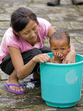 Young Mother Is Washing Her Daughter In A Small Bucket Royalty Free Stock Photos
