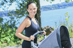 Young mother jogging with a baby buggy Stock Image