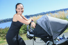 Young mother jogging with a baby buggy Stock Images