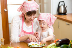 Young mother and kid making funny vegetables dish Royalty Free Stock Photo