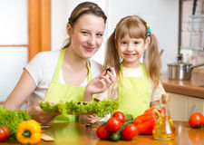 Young mother and kid making vegetable salad Royalty Free Stock Image