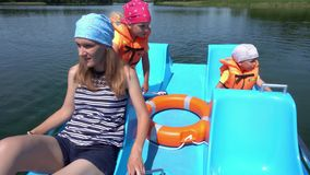 Young mother with kids boy and girl have fun in catamaran boat . Gimbal motion stock video