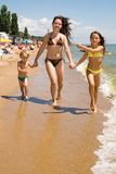 Young mother with kids at the summer resort. Mom and her children enjoying their vacation at the crowded beach Stock Image
