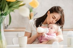 Young woman kiss baby during drinking milk royalty free stock photo