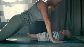Young mother kiss her baby during doing a push ups from floor stock footage