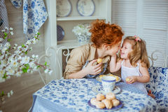 Young mother kiss her little daughter at the desk Stock Photo