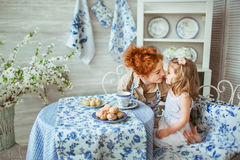 Young Mother Kisses Her Daughter At The Kitchen Royalty Free Stock Image