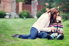Young mother kisses her daughter on the lawn Royalty Free Stock Photo