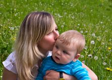 Young mother kisses her little son Royalty Free Stock Images