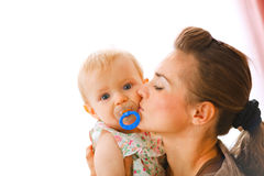 Young mother kissing baby with soother. Young mother kissing baby girl with soother Stock Photos