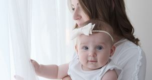 Mother holding baby daughter and looking out through window stock video footage