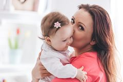 Mother kissing her baby daughter. Young mother kissing her baby daughter. Family love concept. Motherhood Stock Photos