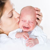 Young mother kissing her crying newborn baby Stock Image