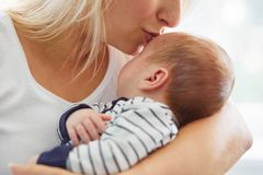 Mother kissing her cute son. A young mother kissing her cute son Stock Photos