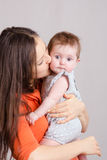 Young mother kissing her daughter. Portrait of mother and baby at the hands of six mothers stock image