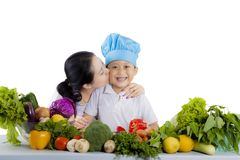 Young mother kissing her little chef Royalty Free Stock Image