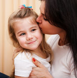 Young mother is kissing her small daughter. Royalty Free Stock Images