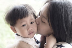 Young mother kissing her son. Young asian mother kissing her son stock images