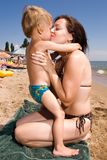 Young mother kissing her son at the beach Stock Photos