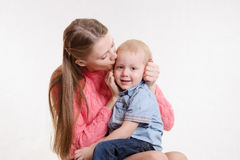 Young mother kissing her son three years. On the lap of a young beautiful girl sits her three year old son Stock Photos
