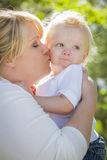 Young Mother Kissing and Holding Her Adorable Baby Boy. In the Park stock photo