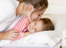 Young mother kissing sleeping daughter at morning Royalty Free Stock Photo