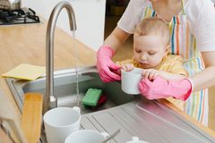 Young mother in a kitchen is washing cups and dishes. Her little son helps stock photos