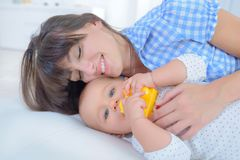 Young mother laying on bed next to baby. Young mother laying on a bed next to her baby Royalty Free Stock Photos