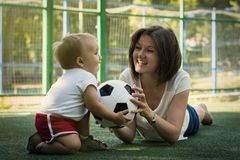 Young mother laying on belly on turf and playing with baby son with soccer ball at football field.  Mom and son have fun together royalty free stock photo
