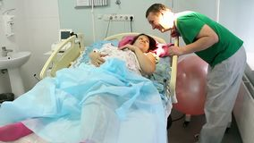 A young mother lies with a newborn in the maternity ward. Relax after childbirth.The happy father kisses her. stock video