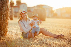 A young mother with  little baby boy in cap sitting on a backgro Royalty Free Stock Images