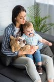 Young mother and little baby with pacifier and teddy bear sitting on sofa. At home stock images
