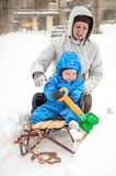 Young mother and little boy enjoying sleigh ride. Child sledding. Toddler kid riding sledge. Children play outdoors in snow. Kids Stock Image