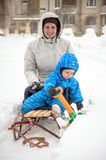 Young mother and little boy enjoying sleigh ride. Child sledding. Toddler kid riding sledge. Children play outdoors in snow. Kids Royalty Free Stock Photo