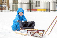 Young mother and little boy enjoying sleigh ride. Child sledding. Toddler kid riding sledge. Children play outdoors in snow. Kids. Sled in snowy park. Outdoor Royalty Free Stock Images