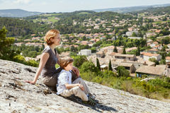 The young mother and little boy sit on mountain slope Stock Photos