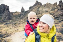 Young mother with little boy travelling in backpack Stock Photos