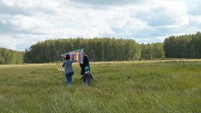 Family with kite outdoor. Young mother, little child and grandfather are going to fly big rzindow kite in the countryside. Active family lesiure outdoor stock footage