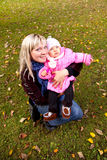 Young mother and little child sitiing on grass in autumn park. Royalty Free Stock Images
