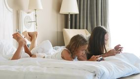 Young mother with little cute daughter are using gadgets lying on a white bed. stock video footage