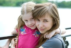 Young mother and little daughter. Happy young mother and her little daughter are hugging Stock Image