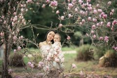 Young mother and little daughter in autumn park play with magnolia leaves. Happy weekend with family in autumnal forest. Young mother and little daughter in royalty free stock photography
