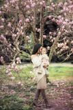 Young mother and little daughter in autumn park play with magnolia leaves. Happy weekend with family in autumnal forest. Young mother and little daughter in stock photography