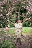 Young mother and little daughter in autumn park play with magnolia leaves. Happy weekend with family in autumnal forest. Young mother and little daughter in stock images