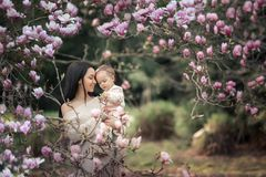Young mother and little daughter in autumn park play with magnolia leaves. Happy weekend with family in autumnal forest. Young mother and little daughter in stock image