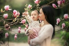 Young mother and little daughter in autumn park play with magnolia leaves. Happy weekend with family in autumnal forest. Young mother and little daughter in stock photos