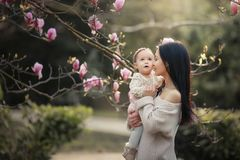 Young mother and little daughter in autumn park play with magnolia leaves. Happy weekend with family in autumnal forest. Young mother and little daughter in royalty free stock photo