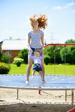 Young mother and little daughter bouncing on trampoline. Beautiful young mother and little daughter bouncing on trampoline Royalty Free Stock Photography