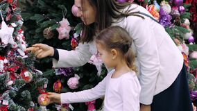 Young mother and little daughter is choosing a Christmas tree in the store. stock video
