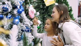 Young mother and little daughter is choosing a Christmas tree in the store. stock video footage